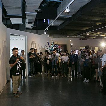 遠雄展覽-藝術家黑雞先生於展作前為觀眾導覽。